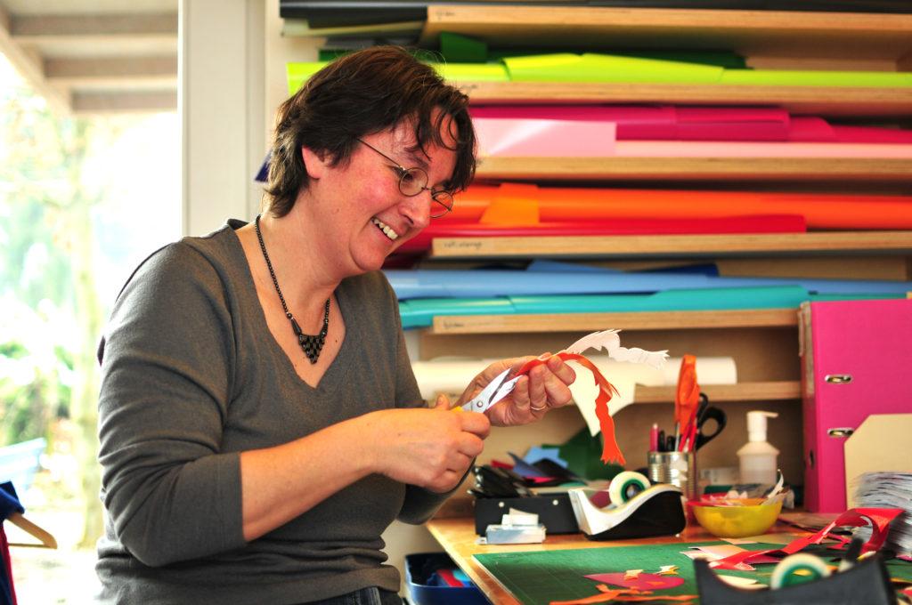 cwirbelwind-Mitarbeiterin Käthi schneidet ein Motiv aus Blachenstoff für ein Chindsgitäschli zu.