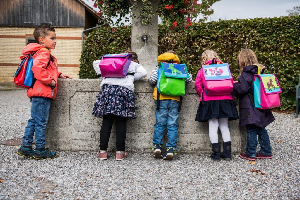 Kinder mit bunten Rucksäcken beugen sich über einen Brunnen